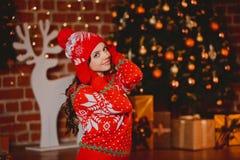 Vinter xmas-stående: Kofta, handskar och hatt för ung kvinna som iklädd röd varm woolen poserar den inomhus near julgranen Fotografering för Bildbyråer