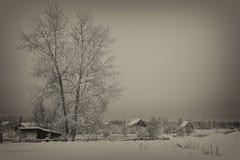 Vinterafton i byn, Ryssland, svartvitt foto, tonad antikvitet arkivfoto