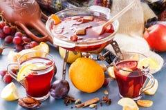 Vinteralkoholdrycker - funderat vin, stansmaskin, toddy Exponeringsglas skorrar med funderat vin varm tea för frukt Kryddor frukt Arkivbild