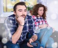 Vinterbegrepp - kvinna som är borrad hållande ögonen på tv med pojkvännen arkivfoton
