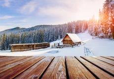 Vinterberglandskap med en snöig skog och en träkoja Arkivbilder