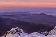 Vinterberglandskap med röd solnedgång fotografering för bildbyråer