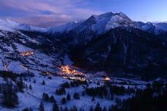 Vinterberglandskap på skymning med snö och byn arkivbilder