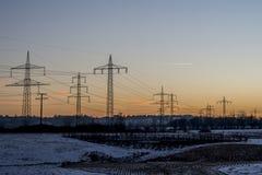 Vinterelkraftlinjer stålsätter gryning 5 för soluppgång för solnedgången för tornlandskapsnö vit Royaltyfri Bild