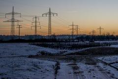 Vinterelkraftlinjer stålsätter gryning 3 för soluppgång för solnedgången för tornlandskapsnö vit Arkivbild