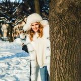 Vinterferie Den lyckliga vinterkvinnan med kastar snöboll utomhus- arkivbild