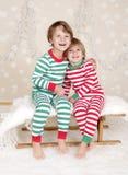 Vinterferier: Skratta lyckliga ungar i julpyjamassläde I Arkivbild