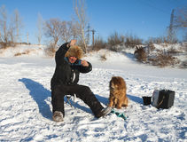 Vinterfiske med en hund Arkivbild