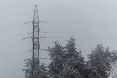 Vinterfoto av det höga anseendet för spänningsöverföringstorn på den gråa himmelbakgrunden med den med is skogen när blizazard Royaltyfri Fotografi