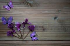 Vinterfotografibild av rosa purpurfärgade cyklamenblommor och roliga leksakfjärilar på lantlig wood bakgrund och utrymme Royaltyfri Fotografi