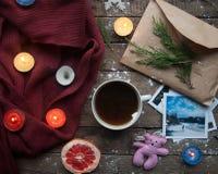 Vintergarnering Sammansättning på wood bakgrund Varmt te, stearinljus, klippt grapefrukt Jul bolljulen isolerade white för mood t Arkivbild