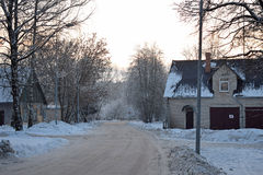 Vintergata i liten by i Lettland Arkivfoton