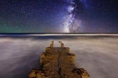Vintergatan över pir på havet Royaltyfri Fotografi