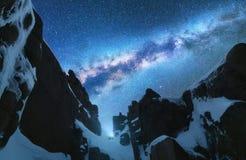 Vintergatan och snöig berg på natten avst?nd arkivbilder
