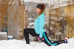 Vintergenomkörare Bärande sportswear för flicka som sträcker övningar royaltyfri bild