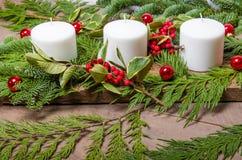 Vintergrön julhöjdpunkt med vita stearinljus Arkivbilder