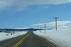 Vinterhuvudväg med telefonpoler Fotografering för Bildbyråer