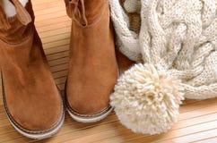 Vinterkängor, hatt och halsduk på golvet arkivfoton