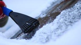 Vinterkörning - skrapande is från en vindruta arkivfilmer