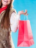 Vinterkvinna med den röda pappers- shoppingpåsen Fotografering för Bildbyråer