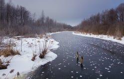 Vinterlandcape med den djupfrysta floden i afton Arkivbilder