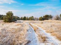 Vinterlandskap av dentäckte grusvägen på en Sunny Day Royaltyfria Bilder