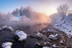 Vinterlandskap: Floden som flödar bland detäckte och Is-täckte stenarna och Rose Sun Rising Over The Forest Pinky W royaltyfri fotografi