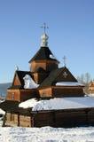 Vinterlandskap med den lilla träbykyrkan mot himlen Royaltyfri Bild
