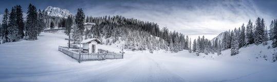 Vinterlandskap med den snöig skogen och kapellet Arkivfoto