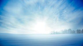 Vinterlandskap med den snöig fält- och resningsolen Arkivbilder