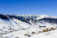 Vinterlandskap med en bergby royaltyfria foton