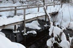 Vinterlandskap med en brige över ström Arkivfoton
