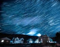Vinterlandskap med stjärnaslingor ovanför hus och skog på natten royaltyfria foton