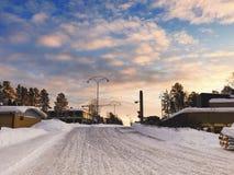 Vinterlandskap med träd och byggnader omkring under den blåa himlen och molnet royaltyfri foto
