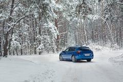 Vinterlandskap med vägen och blåttbilen Royaltyfri Foto