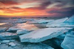 Vinterlandskap på kusten under solnedgång Lofoten öar, Norge Is och solnedgånghimmel royaltyfri bild