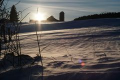 Vinterlantgårdsolnedgång royaltyfria bilder
