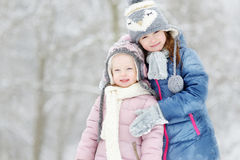 Vintern för två parkerar den roliga förtjusande lilla systrar Arkivfoto