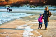 Vintern går vid det baltiska havet, modern och dottern Fotografering för Bildbyråer