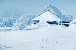 Vintern landskap med det snöig hemmet Royaltyfria Bilder