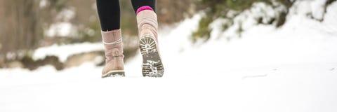 Vintern äventyrar - closeupen av varmt kvinnligt gå för vinterkängor Arkivfoto