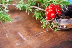 Vinterplatsen med nya gröna filialer av sörjer, järnek, en, kottar, stjärnan, röd bärbarberry i naturligt trä Royaltyfria Foton