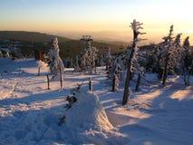 Vinters solnedgång i de snöig bergen Arkivbilder