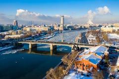 Vintersikt av den Moskva floden, den Novospasskiy bron och skyskrapor på en solig morgon Isisflak, kvarter av is, snö på tak royaltyfri bild