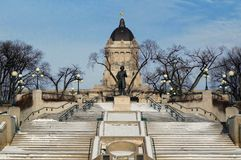 Vintersikt från banken av den Assiniboine floden på Manitoba lagstiftande församlingbyggnad med Louis Riel skulptur framme royaltyfri fotografi