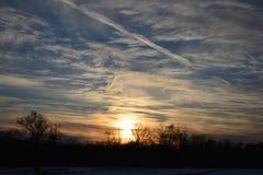 Vintersolnedgång över fält med wispy moln Royaltyfri Bild