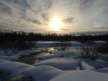 Vintersolnedgång över floden Arkivfoton
