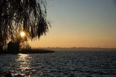 Vintersolnedgång på sjön Himmel med varmt aftonljus fotografering för bildbyråer