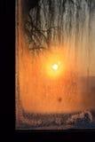 Vintersoluppgång på det smutsiga fönstret Arkivfoto