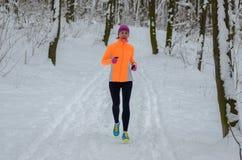 Vinterspring i skog: lycklig kvinnalöpare som joggar i snö, utomhus- sport Royaltyfri Foto